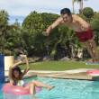 Man Jumping Into Swimming Pool Over Woman On Ring — Stock Photo #21790243