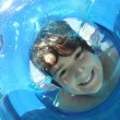 Stock Photo: Boy Looking Through Inflatable Ring In Water