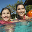 Mother And Daughter Enjoying In Pool - Zdjcie stockowe
