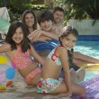Family Sitting Together At The Edge Of Pool - Foto de Stock  