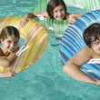 Siblings With Inflatable Rafts Enjoying Together In Swimming Pool — Stock Photo