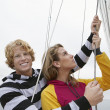 Young Couple Holding Rigging On Sailboat — Stock Photo #21790569