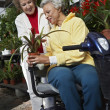 Woman Selling Plant To Disabled Woman At Botanical Garden — Stock Photo