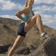 Stock Photo: Female Jogger Stretching On Rock