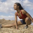 Stock Photo: Female Jogger Stretching In Mountains