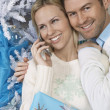 Woman using cell phone with man embracing her by Christmas tree - Stock Photo