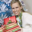 Woman Taking Presents By Christmas Tree — Stock Photo