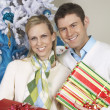 Couple Standing Together With Christmas Gifts — Stock Photo #21792149
