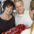 Woman Offering Christmas Present To Happy Couple — Stock Photo