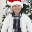 Man In Santa Cap Holding Gift Box By Christmas Tree — Stock Photo
