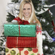 Woman Carrying Stack Of Gifts Against Decorated Christmas Tree — Stock Photo