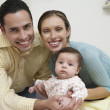 Portrait Of Parents With Baby At Home - Stock Photo