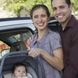 Happy Couple With Baby In Carrier — Stock Photo