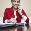 Stock Photo: Woman On Call Taking Notes