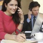 zakenvrouw schrijven tijdens het communiceren op mobiele telefoon — Stockfoto