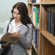 Stock Photo: Female Reading Book In Library