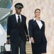 Pilot And Flight Attendant Walking Outside Building - Stock Photo