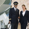 Stock Photo: Pilot And Flight Attendant Outside Building