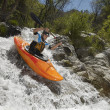 Man Kayaking On Mountain River - Stock Photo