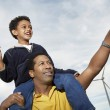 Boy With Paper Plane Sitting On Father's Shoulders — Foto Stock