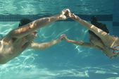 Feliz pareja tomados de la mano en la piscina bajo el agua — Foto de Stock