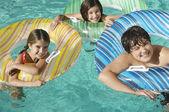 Hermanos con inflable balsas disfrutar juntos en piscina — Foto de Stock