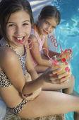 Hermanas beber jugo junto a piscina — Foto de Stock