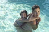 Mother Giving Daughter Piggy Back In Swimming Pool — Stock Photo