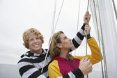 Young Couple Holding Rigging On Sailboat — Stock Photo