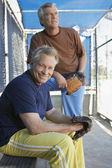 Hombres con manoplas en refugio de béisbol — Foto de Stock
