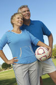 Couple Holding Soccer ball Looking away — Stock Photo