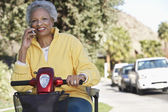 Woman Using Cell Phone On Motor Scooter — Stock Photo