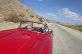 Couple In Classic Car On Desert Road — Stock Photo