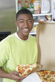 Teenage Boy Holding A Piece Of Pizza — Stock Photo