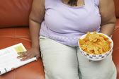Obézní žena s miskou nachos — Stock fotografie