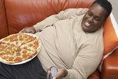 Uomo, guardando la tv con pizza giro — Foto Stock