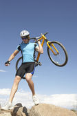 Young Man Carrying Bicycle On Rocks — Stock Photo