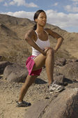 Female Jogger Stretching On Rock — Stock Photo