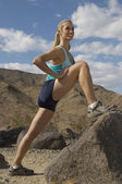 Female Jogger Stretching On Rock — Stockfoto