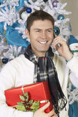 Man Using Cell Phone Holding Present By Christmas Tree — Stock Photo