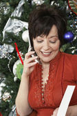 Woman Using Cell Phone By Christmas Tree — Stock Photo