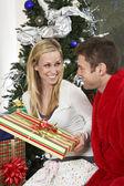 Par med nuvarande sitter av julgran — Stockfoto