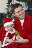 Father And Son In Santa Claus Outfit Holding Present — Stock Photo