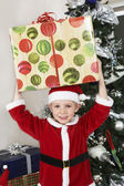 Boy In Santa Claus Outfit Carrying Present On Head — Stock Photo
