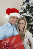 Happy Couple With Gift box standing By Christmas Tree — Stock Photo