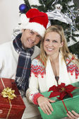 Couple Holding Gifts In Front Of Christmas Tree — Stock Photo