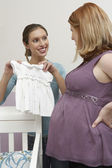 Woman Showing Baby Clothes To A Pregnant Friend — Foto de Stock