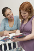 Two Women Looking At Book By Cradle — Stock Photo