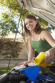 Woman Pouring Oil Into Car Engine — Stock Photo