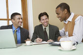 Three Business Men Discussing At Desk — Stock Photo